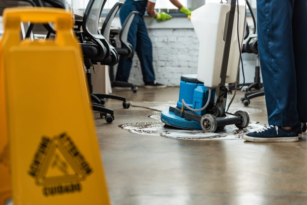 cropped view of cleaner washing floor with cleaning machine near colleague